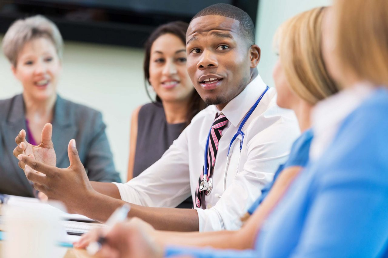 man gestures while talking to colleagues at conference room table