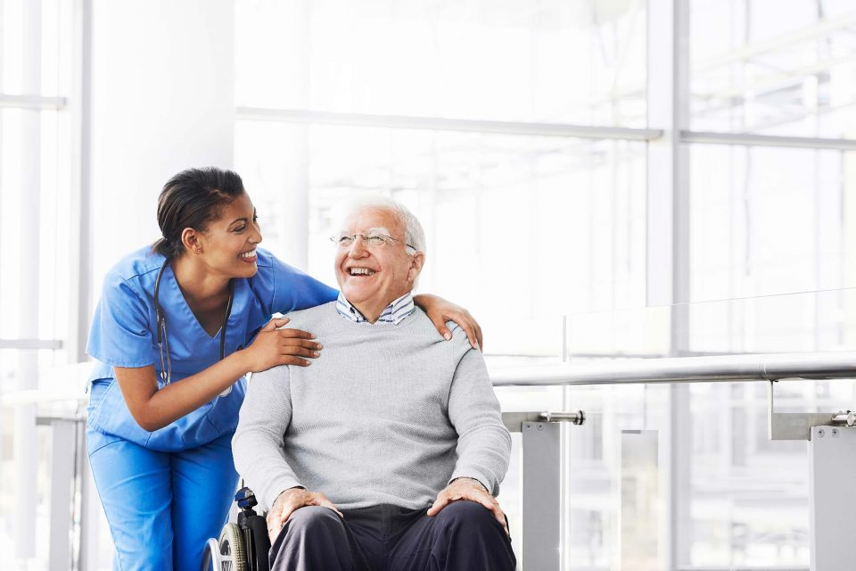nurse in blue scrubs hugs older man in wheelchair