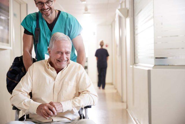 male nurse pushes older gentleman down hallway in wheelchair