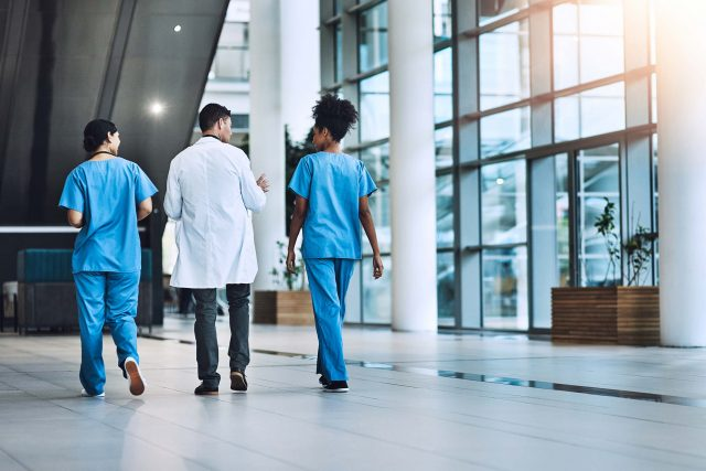 medical practitioners have a conversation walking down hallway of hospital