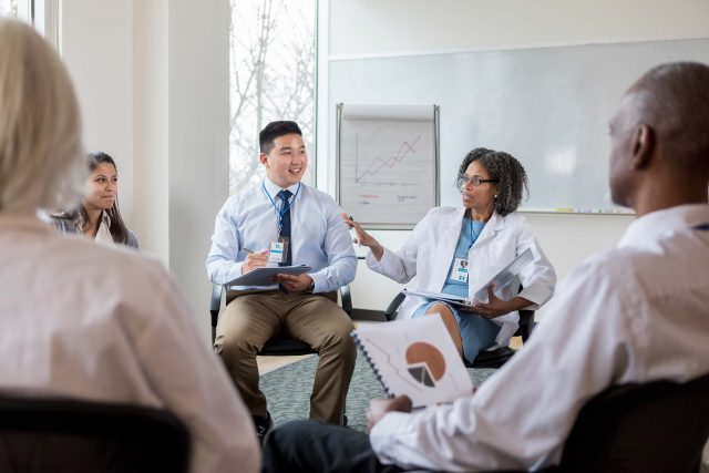 mature female doctor conducts a group conversation with colleagues