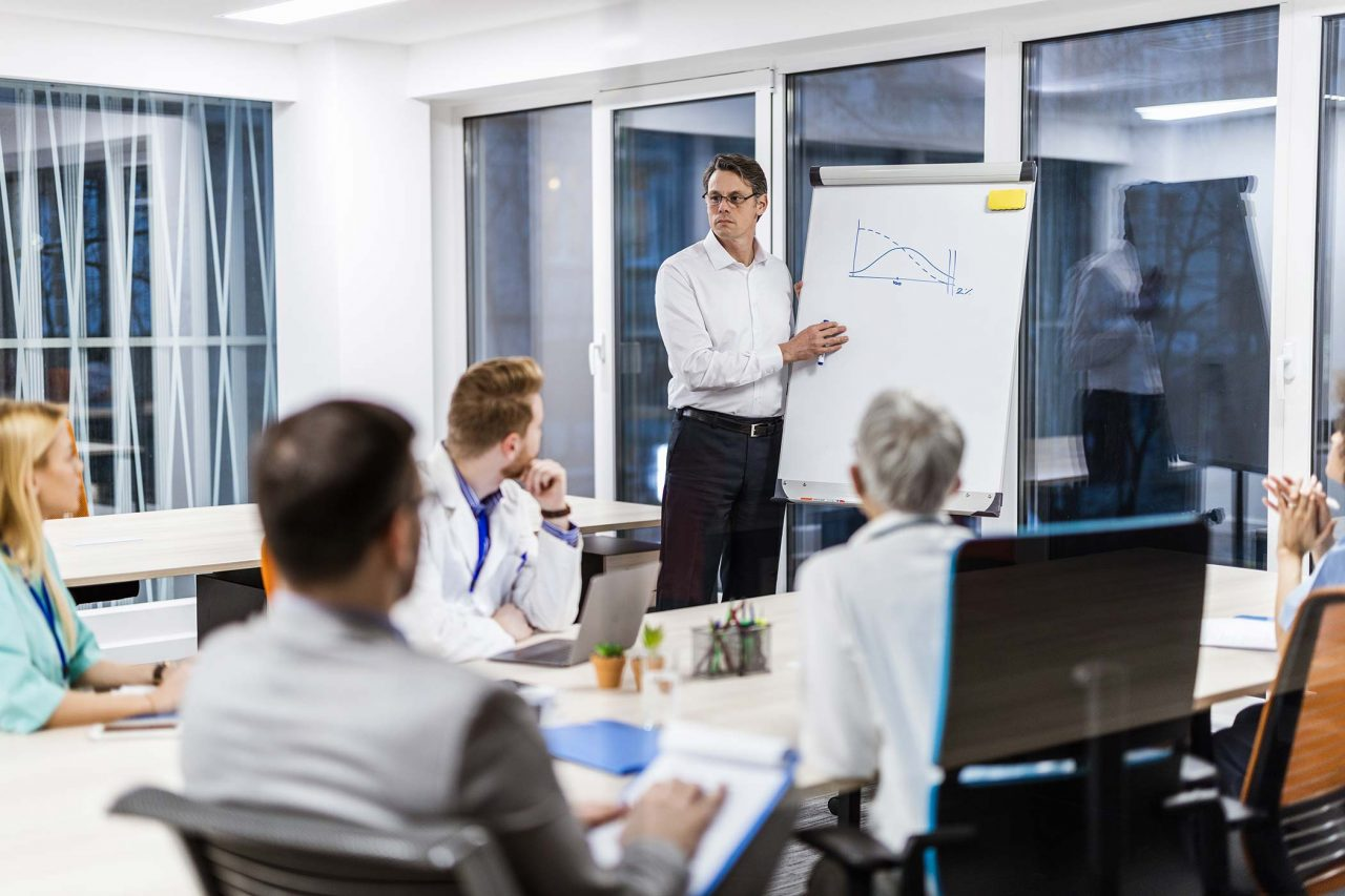 man gives presentation at white board to medical professionals in conference room