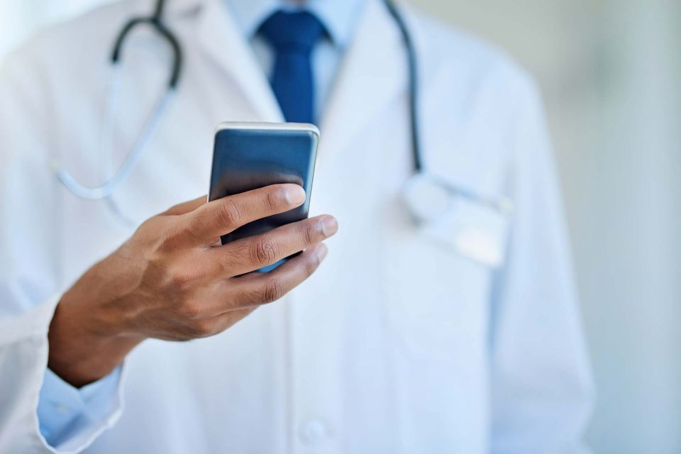 doctor looking down at cell phone