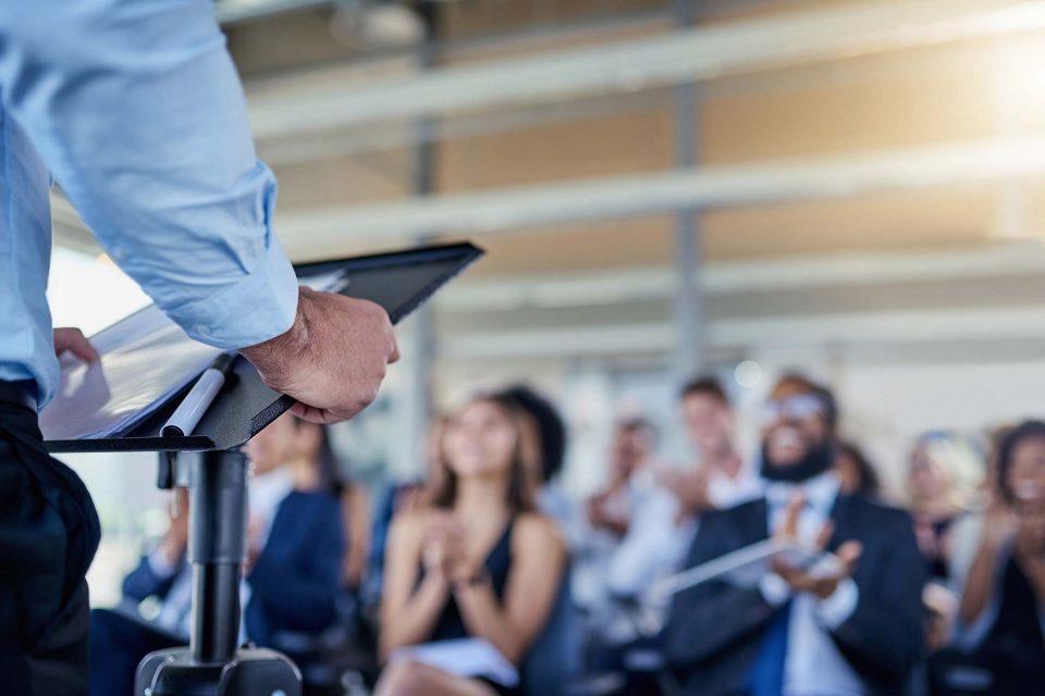 man grips podium while speaking to group of professionals