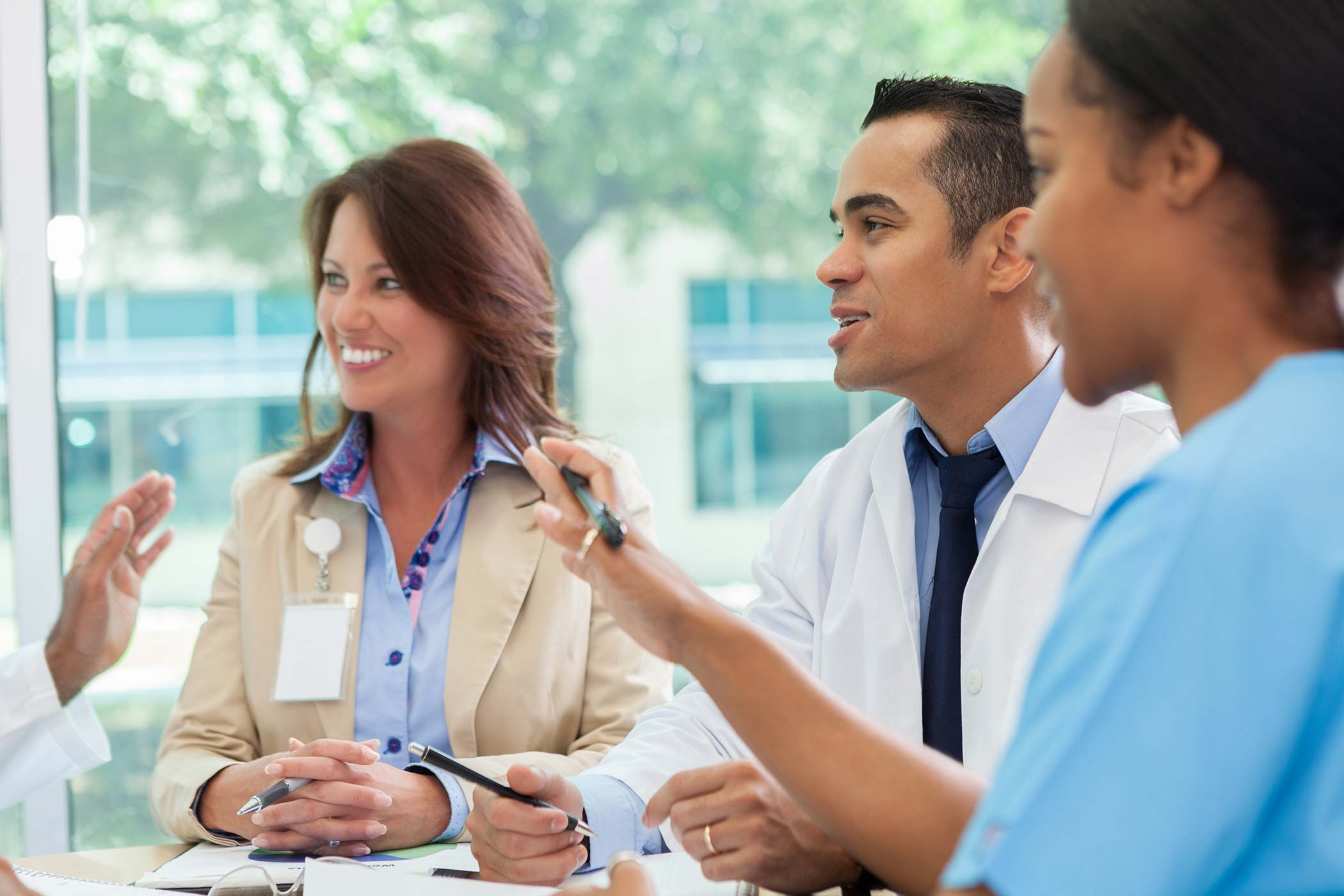 group of medical professionals having a conversation around table