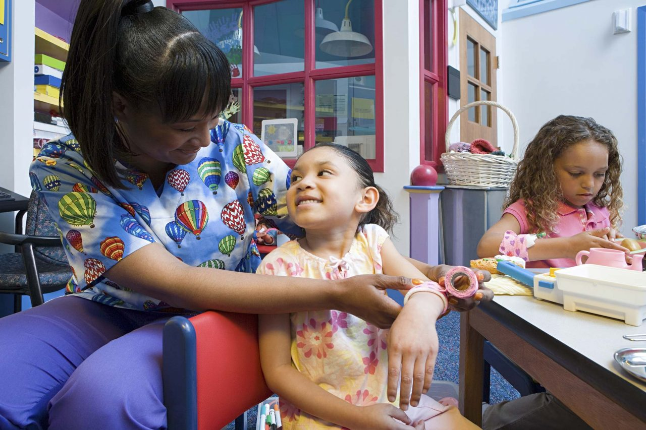 nurse in colorful scrubs works with young girl