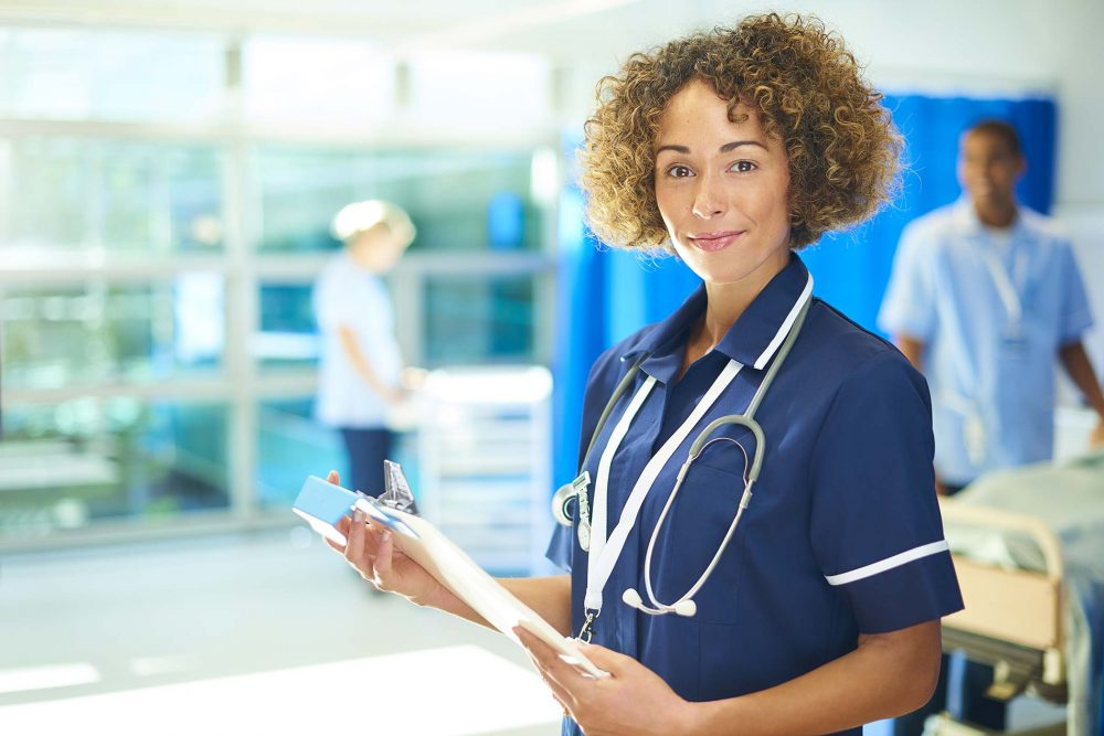 A matron nurse smiles to camera from a busy hospital ward