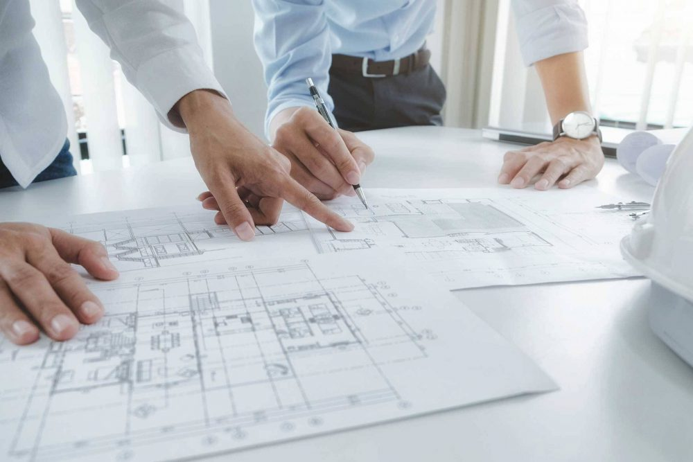 architects lean over desk to review floorplans