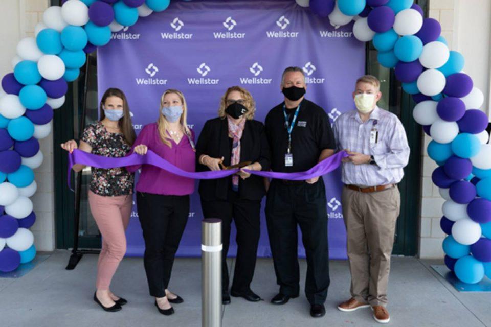 Jon Huddy cuts purple ribbon with Wellstar team wearing masks to celebrate opening of trauma center